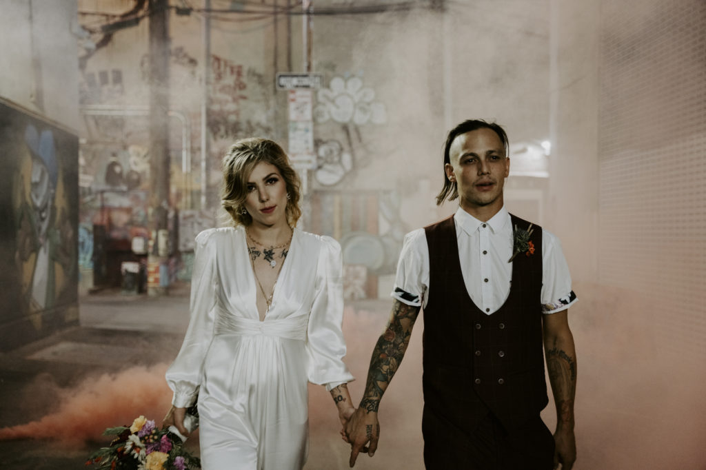 Just eloped couple walking hand in hand in plume of smoke.